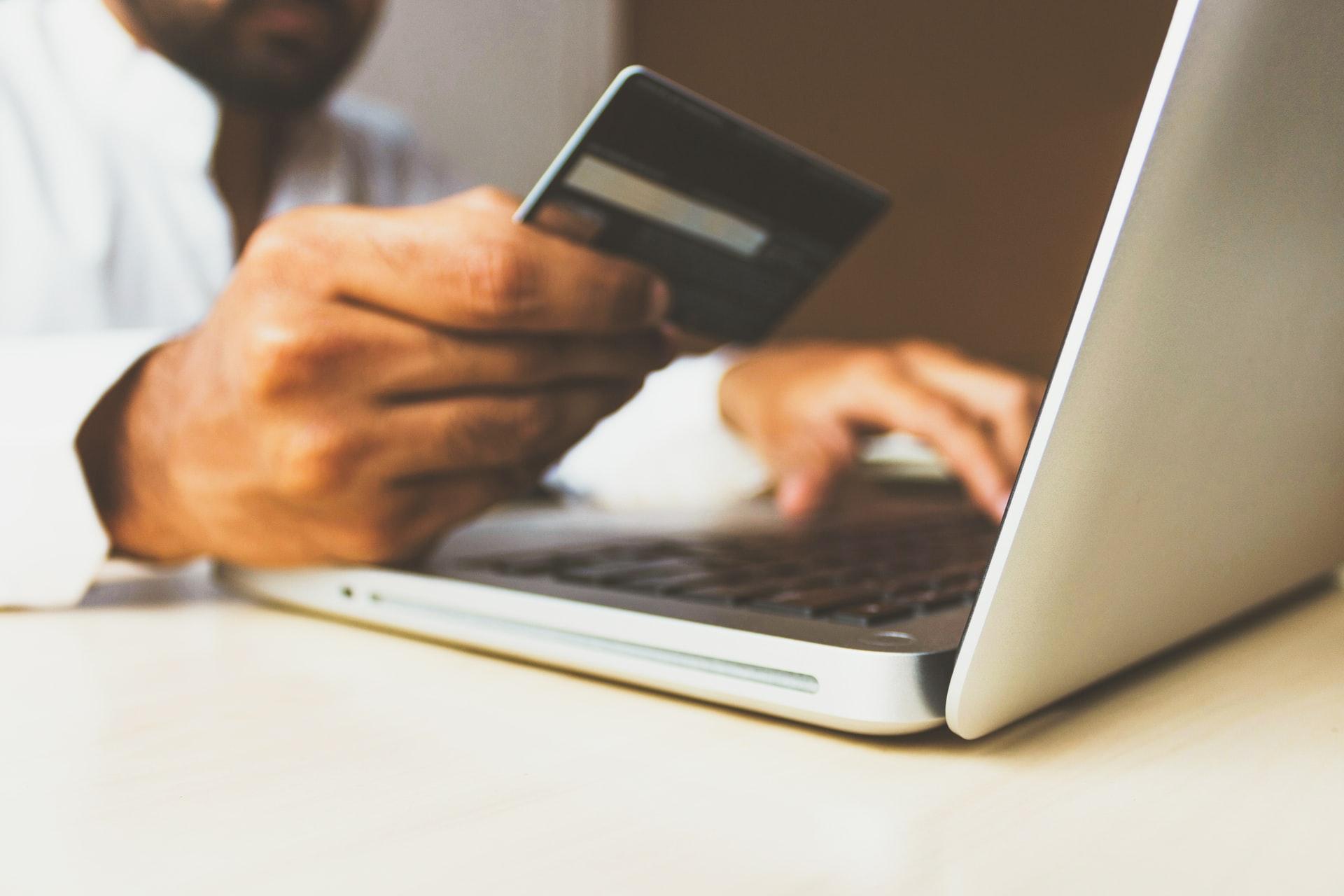 Man betalar med sitt kontokort via laptop