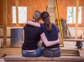 Två kvinnor omfamnar varandra i hus under konstruktion