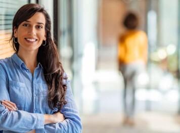 Kvinna i blå blus med korsade armar